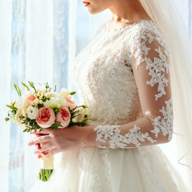 A beautiful bride is holding a wedding bouquet with white roses and peach peonies on a bright window background. Close-up, indoor